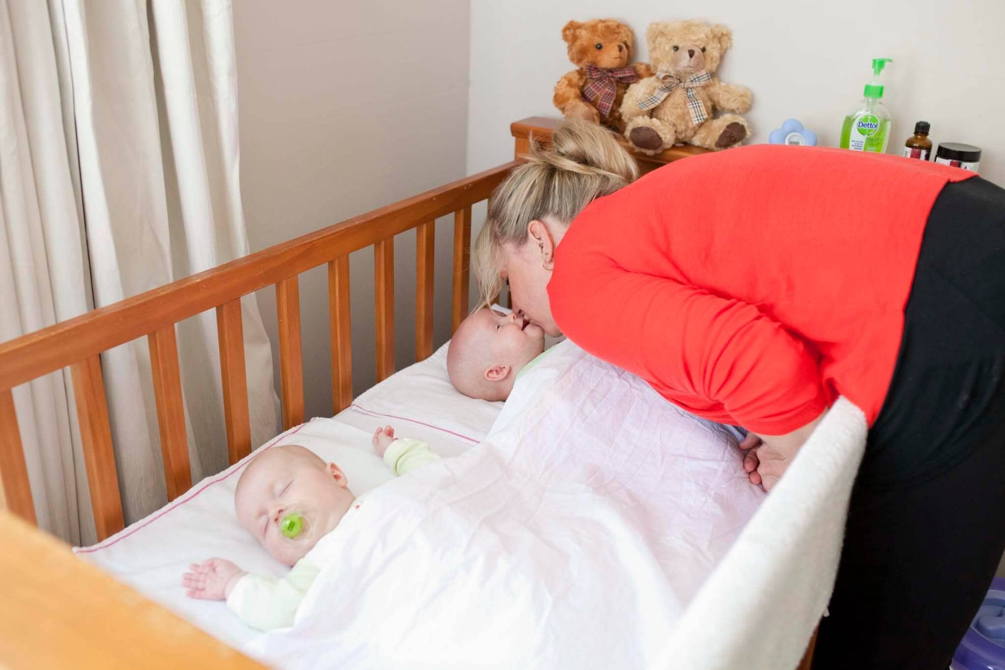 Twins Sleeping in Cot